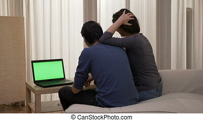 Smiling couple sitting on the edge of the bed looking at a laptop with green screen while having a great conversation and showing affection