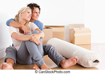 Smiling couple sitting on the floor