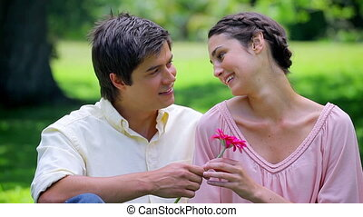 Smiling couple sitting on the grass with a pink flower
