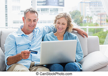 Smiling couple sitting on their couch using the laptop to...
