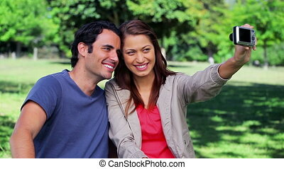 Smiling couple sitting while photographing themselves in a...