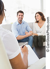 Smiling couple speaking with their therapist