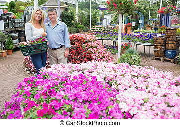 Smiling couple standing in the garden centre