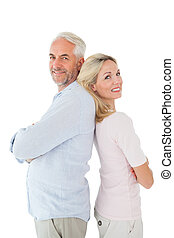 Smiling couple standing leaning backs together