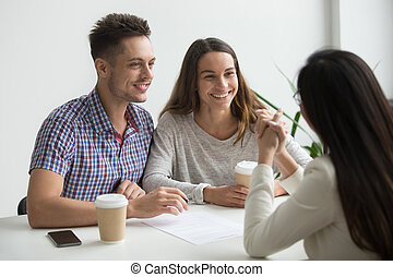 Smiling couple talking to real estate agent
