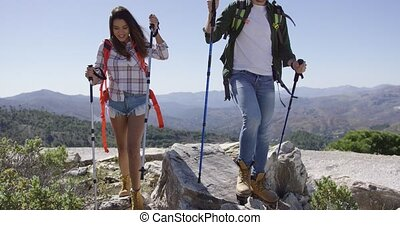 Smiling couple trekking - Two young smiling people walking...