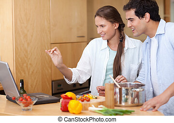 Smiling couple using a laptop to cook in their kitchen