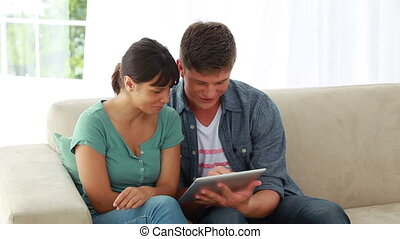 Smiling couple using an ebook together