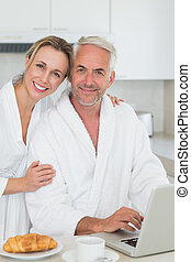 Smiling couple using laptop at breakfast in bathrobes at...