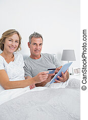Smiling couple using their tablet p