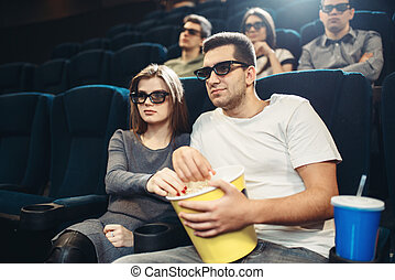 Smiling couple watching comedy movie in cinema