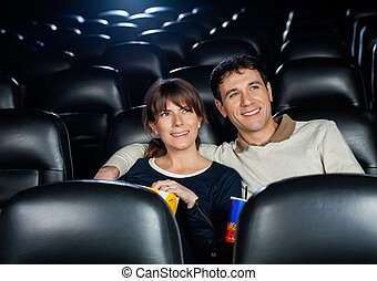 Smiling Couple Watching Film In Theater