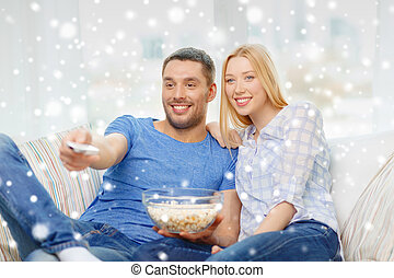 smiling couple watching tv at home