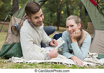 Smiling couple with a map lying in