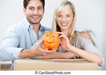 Smiling couple with a piggy bank