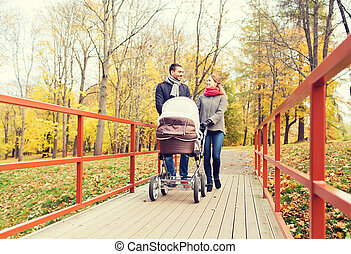 smiling couple with baby pram in autumn park - love,...