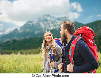 smiling couple with backpacks hiking - adventure, travel,...