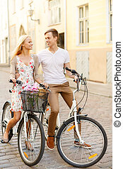 smiling couple with bicycles in the city - summer holidays,...