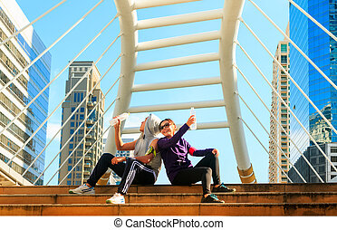 Smiling couple with bottles of cold drink outdoors after sport exercise.