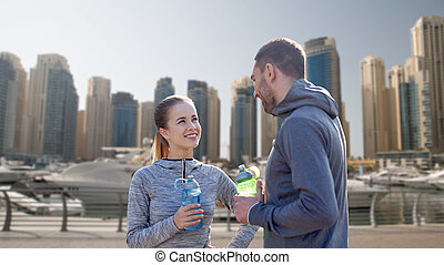 smiling couple with bottles of water in city
