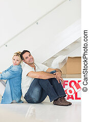 Smiling couple with boxes in a new house