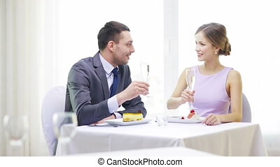 smiling couple with champagne at restaurant