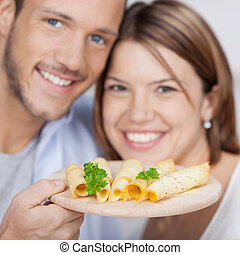 Smiling couple with cheese plate