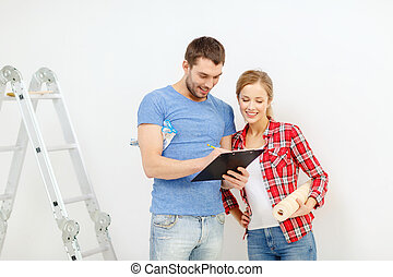 smiling couple with clipboard and wallpaper roll - repair,...