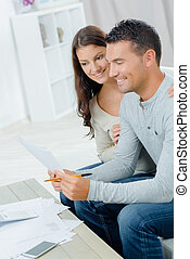 smiling couple with documents in home