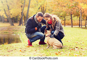 smiling couple with dog in autumn park - care, animals,...