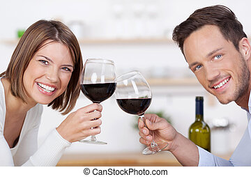 Smiling couple with glasses of red wine