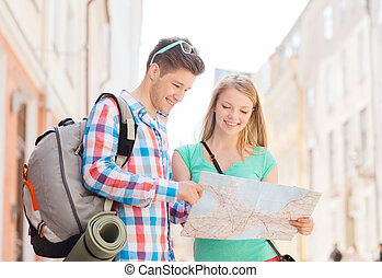 smiling couple with map and backpack in city