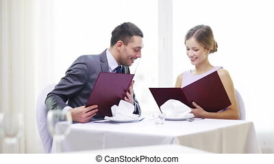 smiling couple with menus at restaurant - restaurant,...
