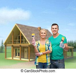 smiling couple with paintbrush