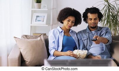 smiling couple with popcorn watching tv at home - people,...