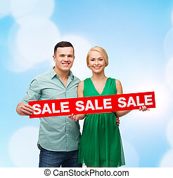 smiling couple with sale sign