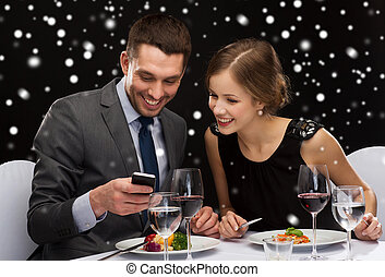 smiling couple with smartphone at restaurant