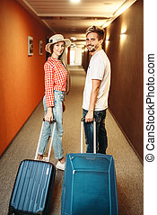 Smiling couple with suitcase in hotel hallway