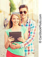 smiling couple with tablet pc in city