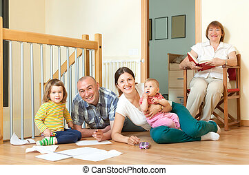 Smiling couple with their offspring and grandmother on floor at