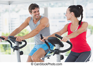 Smiling couple working out at spinn