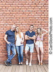 Smiling couples leaning on brick wall