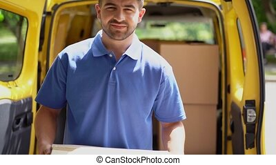 Smiling courier take the package out of van and shows ok...