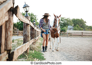 Smiling cowgirl holding and walking with her horse on ranch...