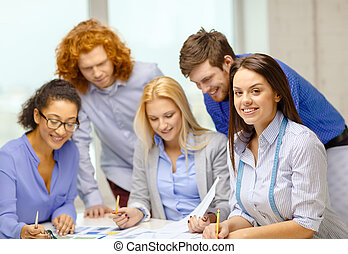 smiling creative team looking over clothes designs