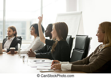 Smiling curious businesswoman raising hand at group meeting voti