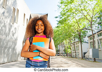 Smiling curly African girl with textbook happy