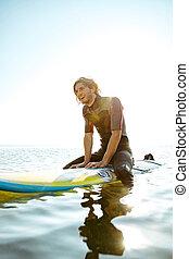 Smiling curly surfer man in swimwear sitting on surf board -...