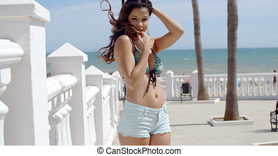 Smiling curvaceous young woman at the seaside