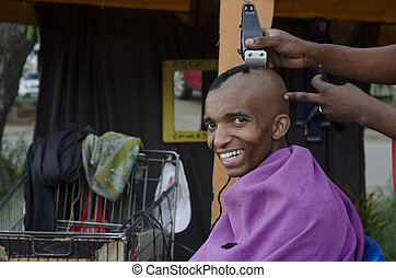Smiling customer at African small haircut barber business -...